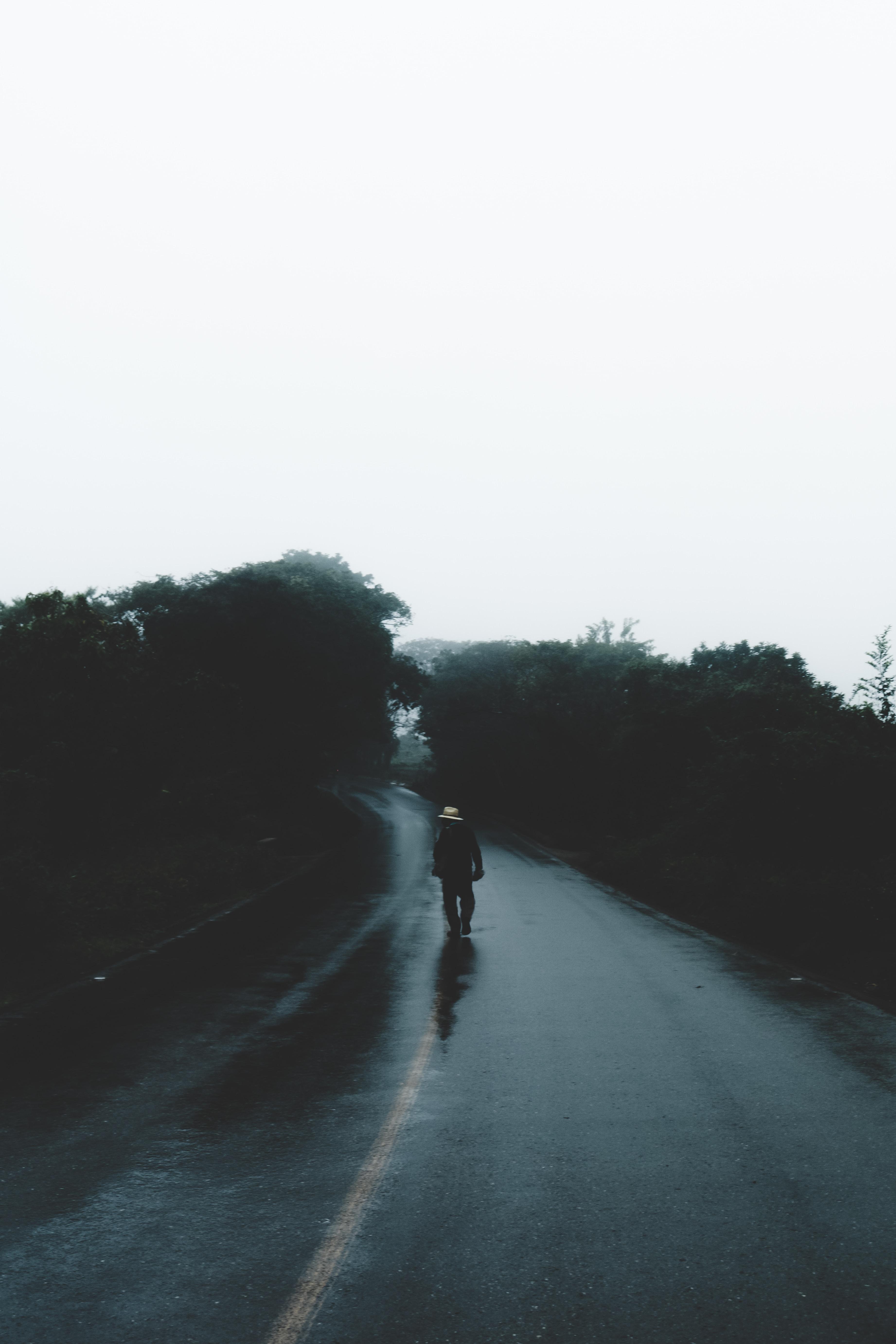 man walking in asphalt road