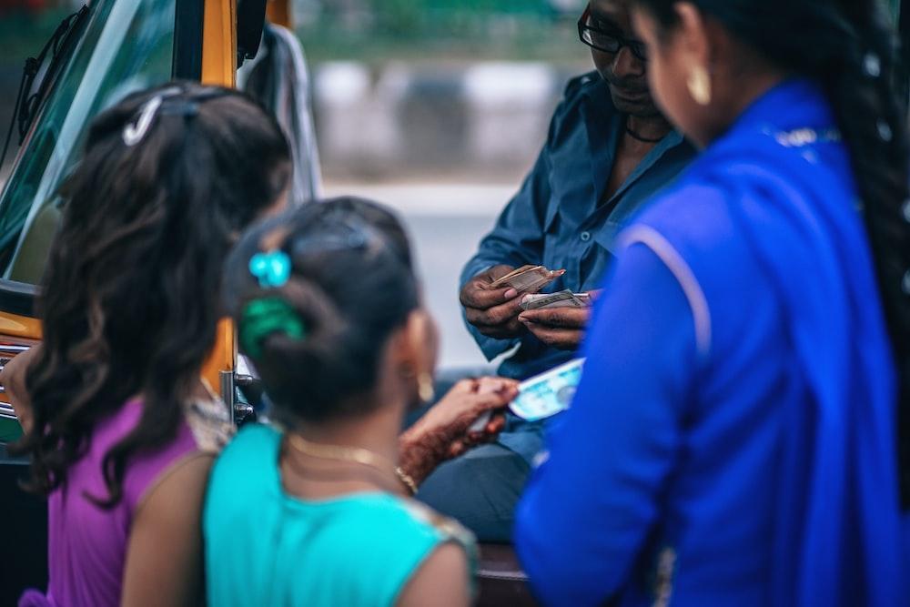 woman beside the two girls standing beside auto-rickshaw