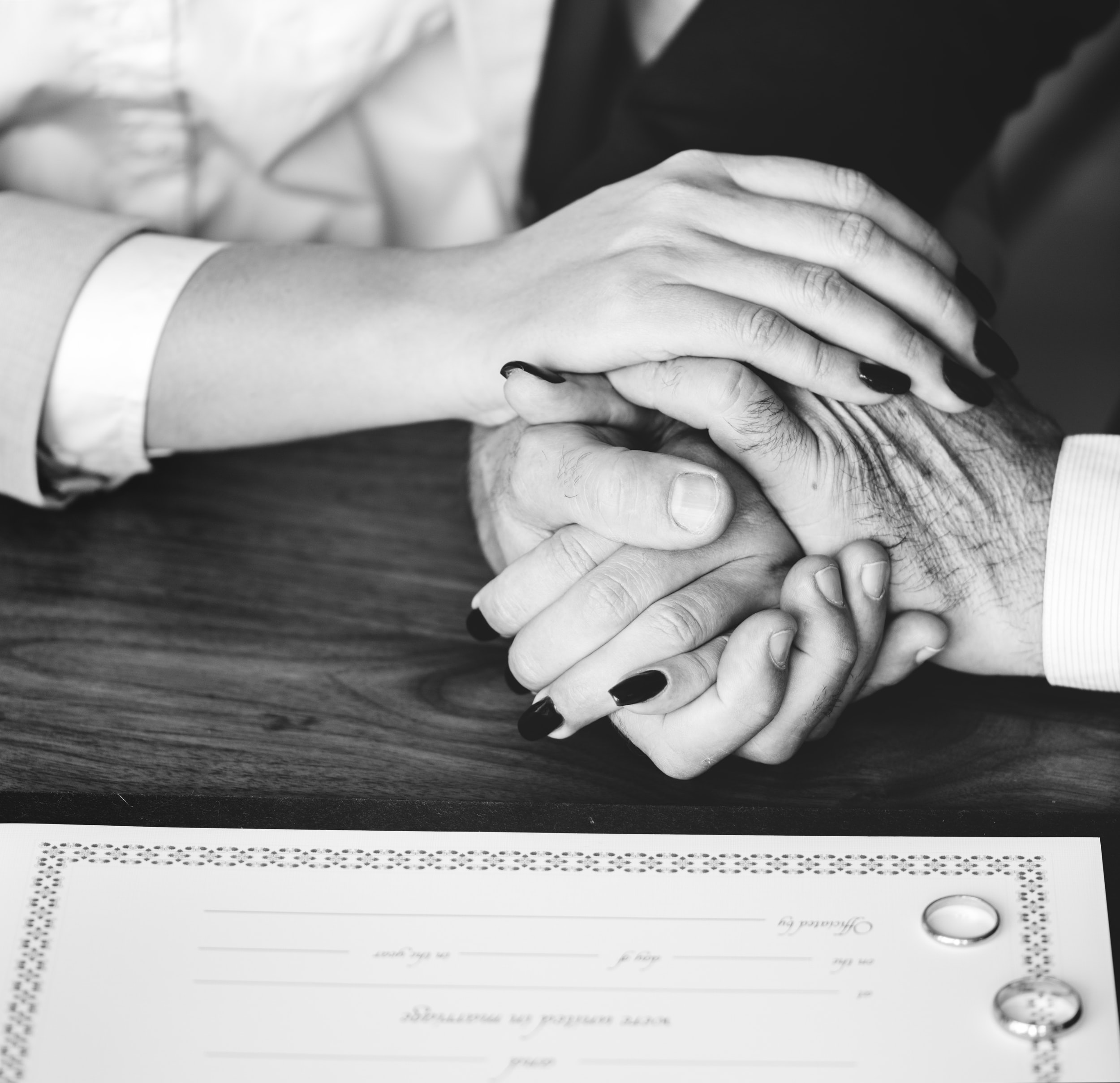 grayscale photo of two person hand holding hands beside two rings