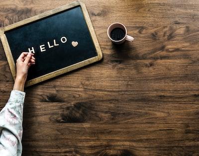 HELLOの文字を手に取りテーブルの板の上に並べている様子