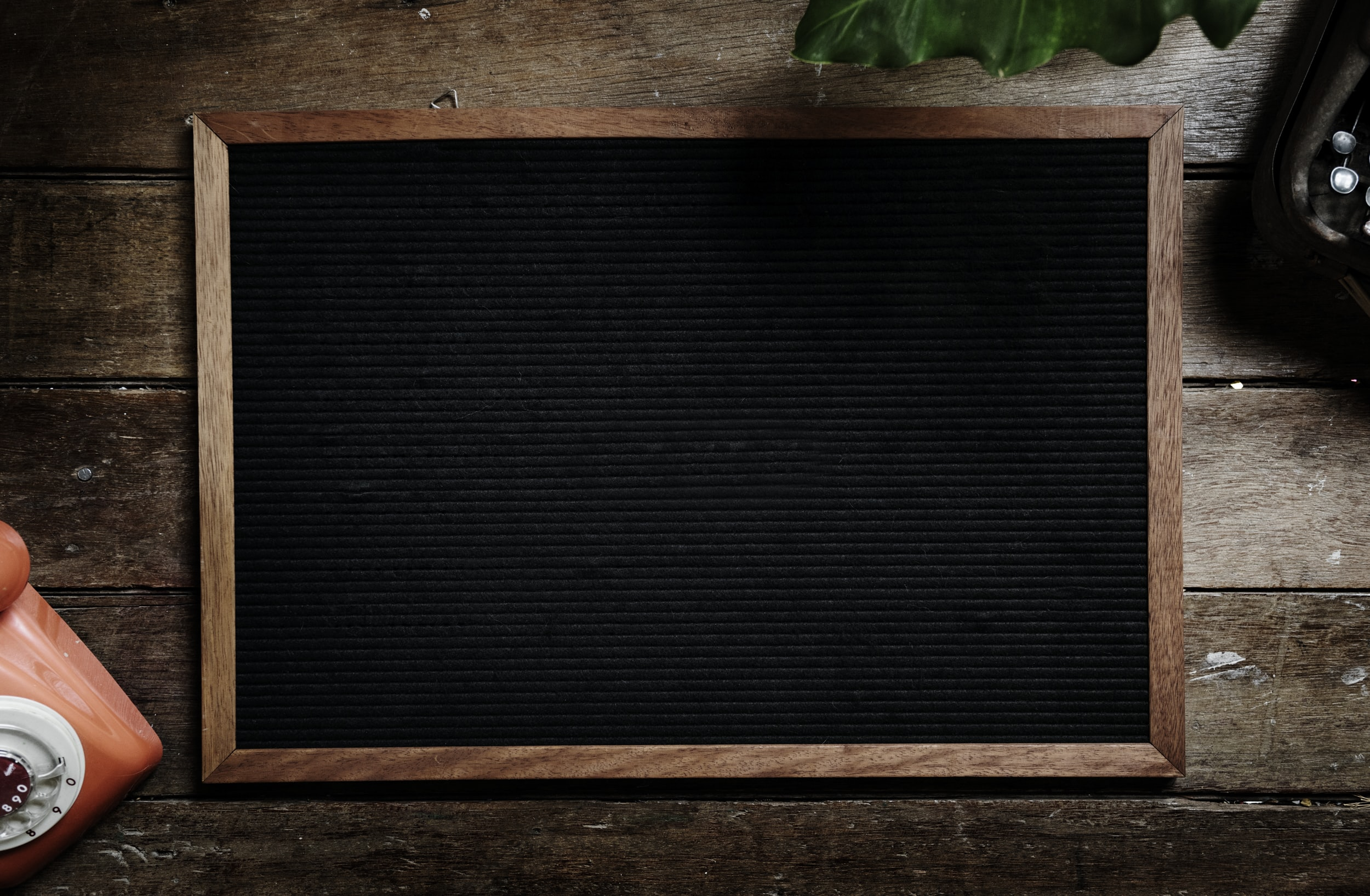 rectangular black board on brown wooden surface