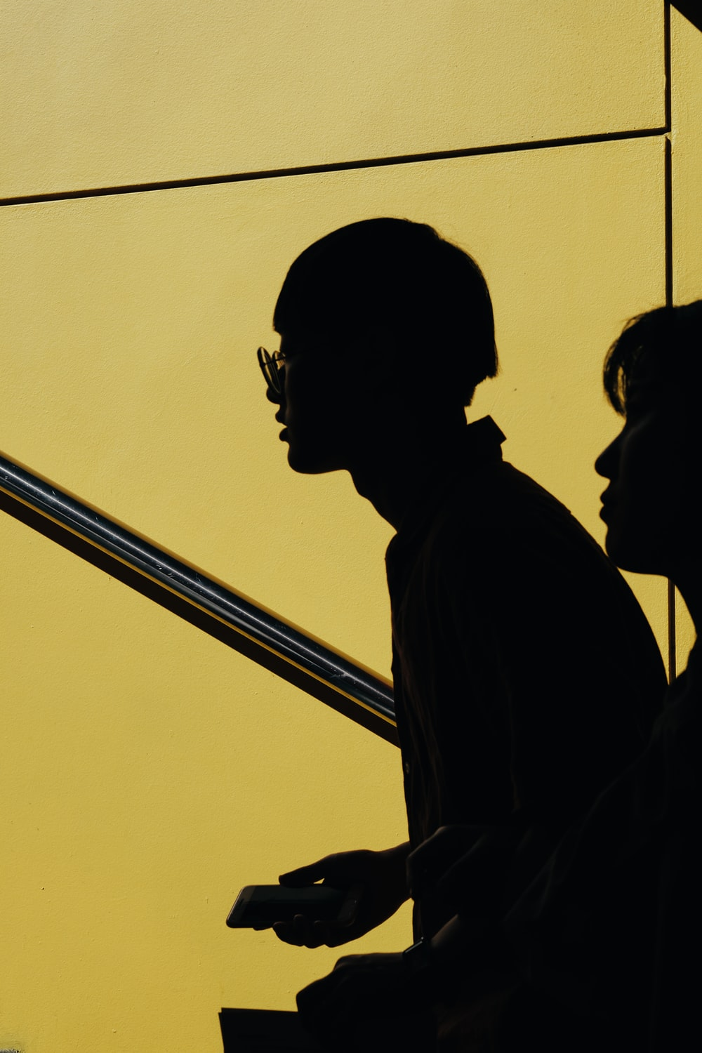 silhouette of two person against yellow background