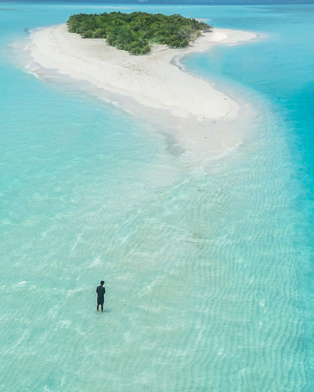 bird's eye view photography of man standing on body of water