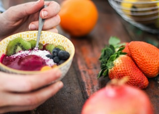 person holding sliced fruit salad on yellow bowl
