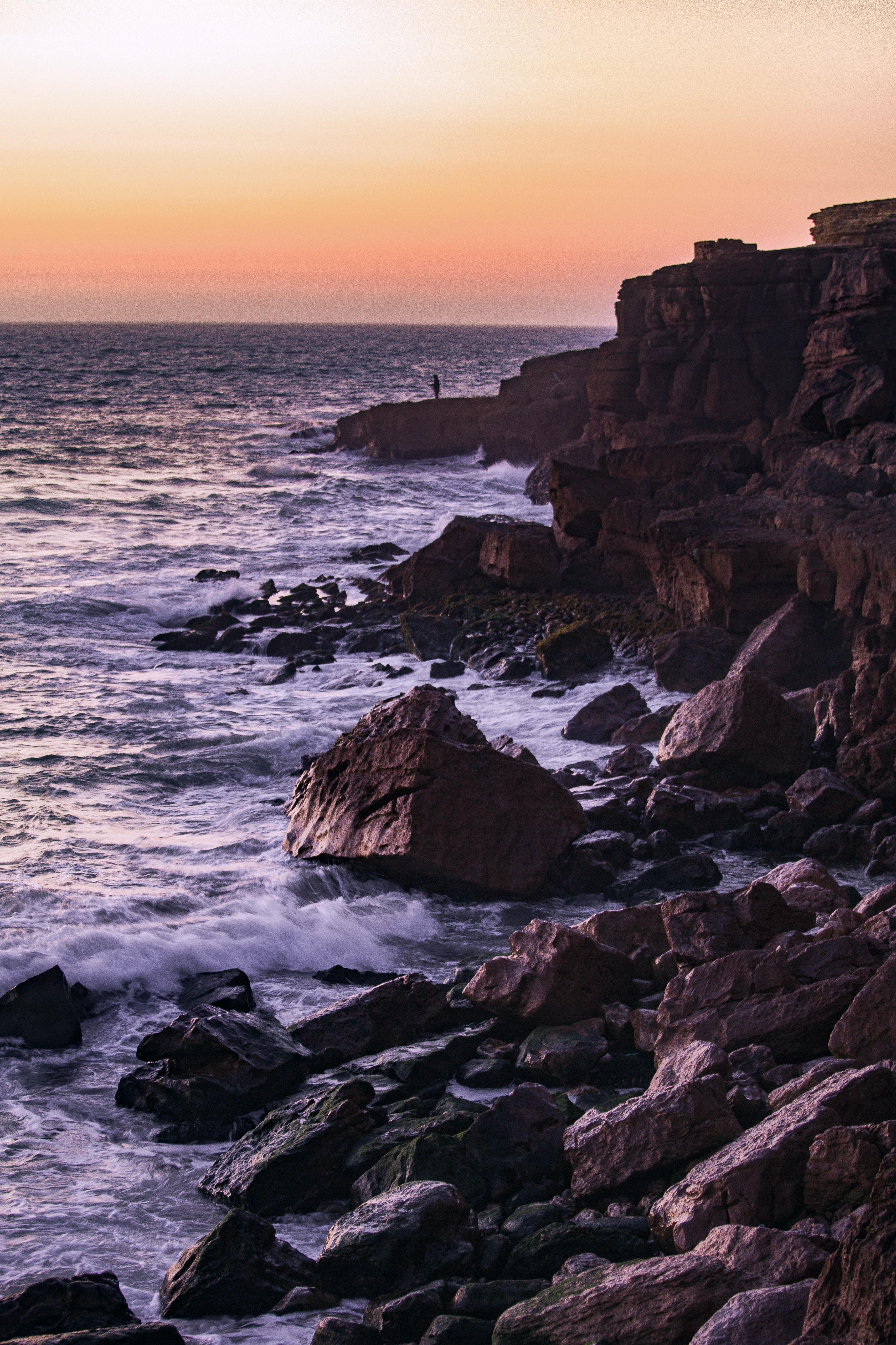 rocks near sea during golden hour