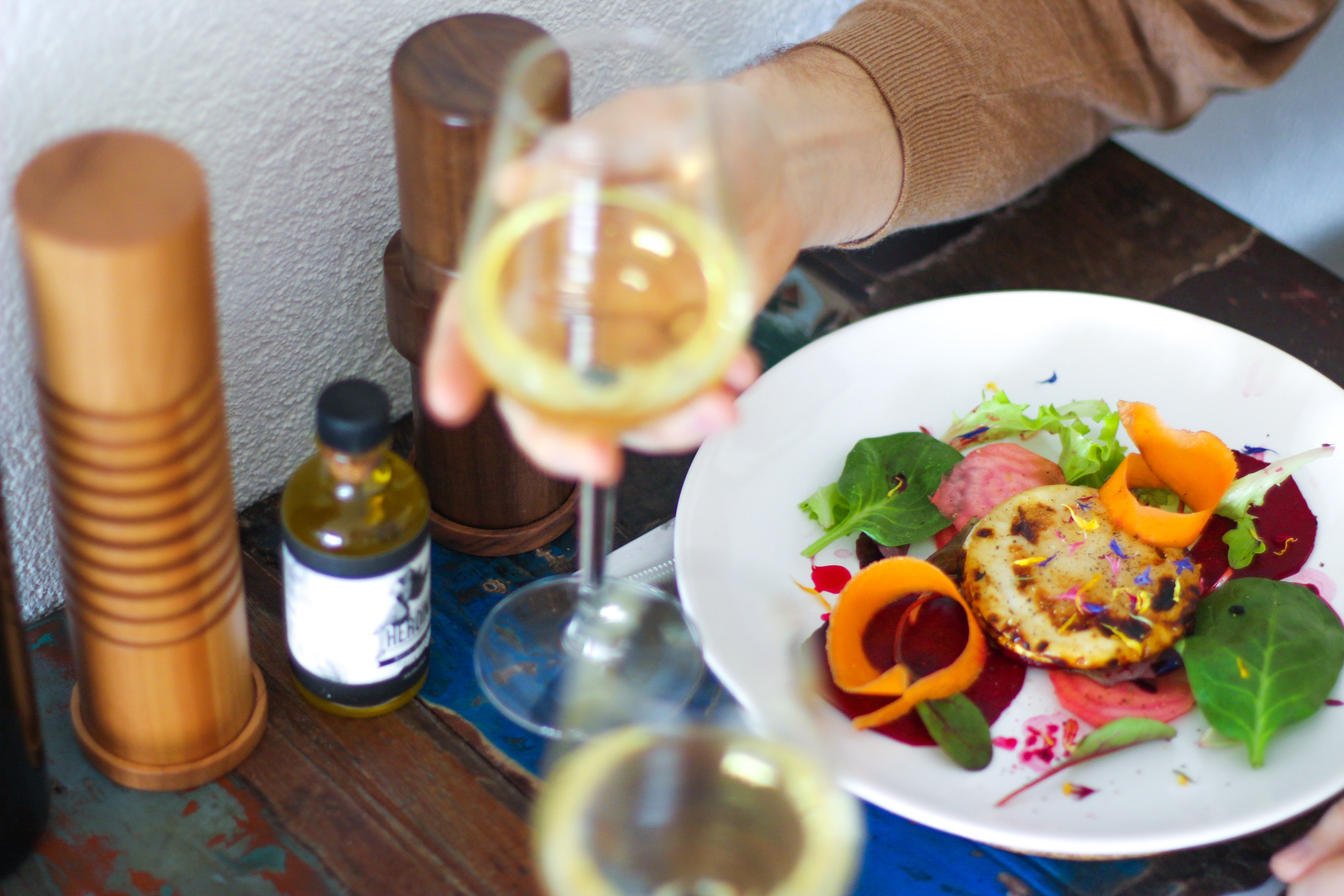 person holding wine glass in front of vegetable salad