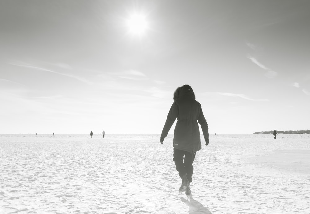 silhouette of woman standing on beach during daytime