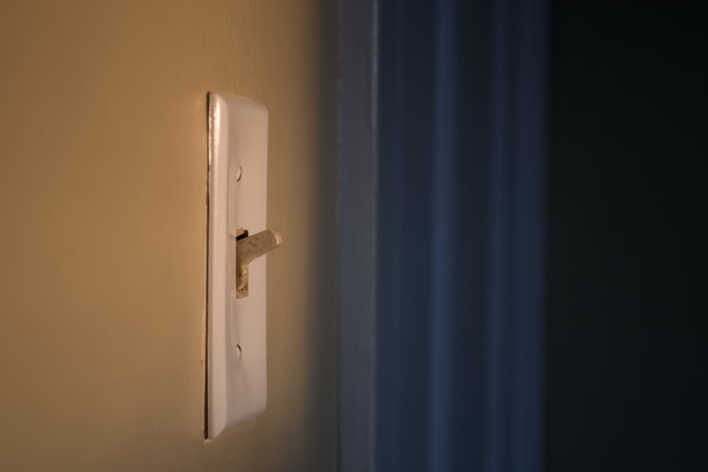 white switch mounted on blue wall