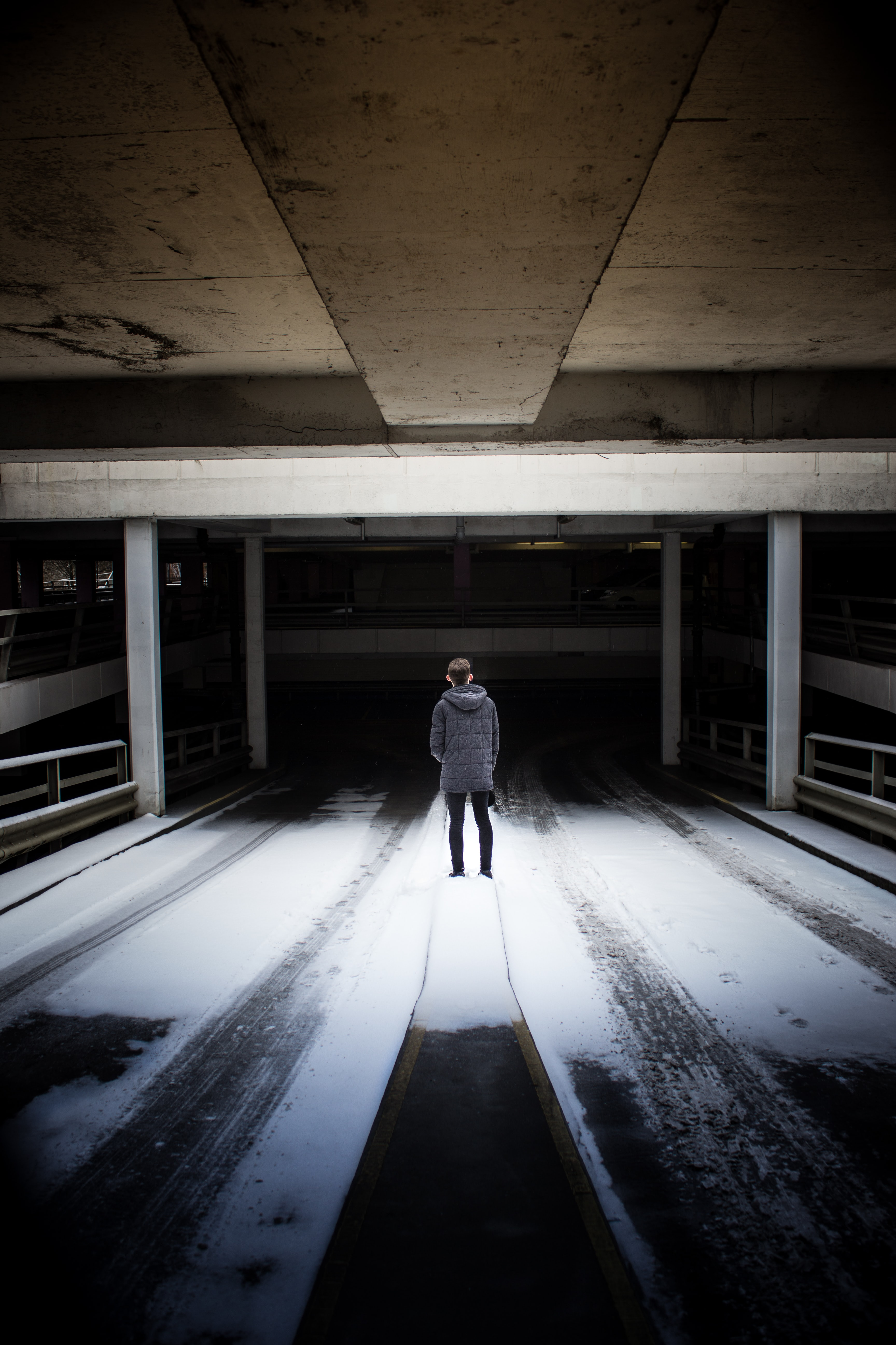 man standing under gray concrete ceiling