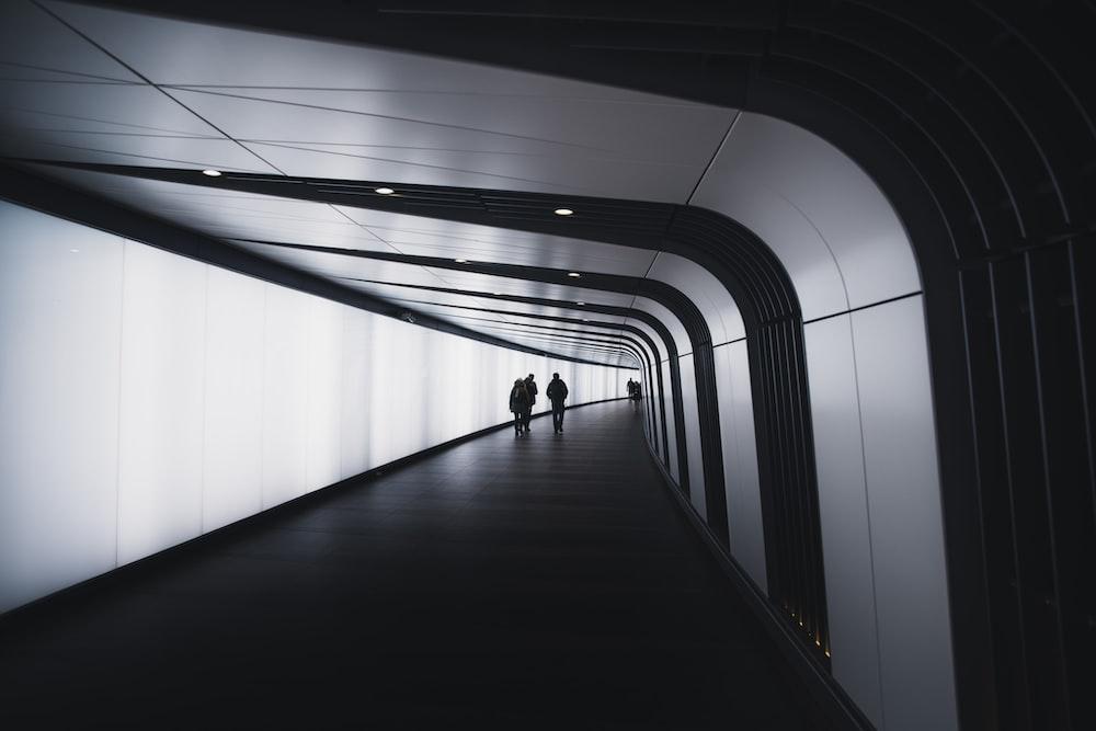 three people walking on corridor