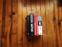 top angle-view of five assorted-title books on brown wooden plank surface