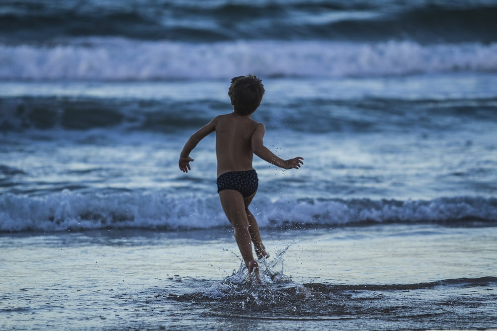 boy running towards seashore