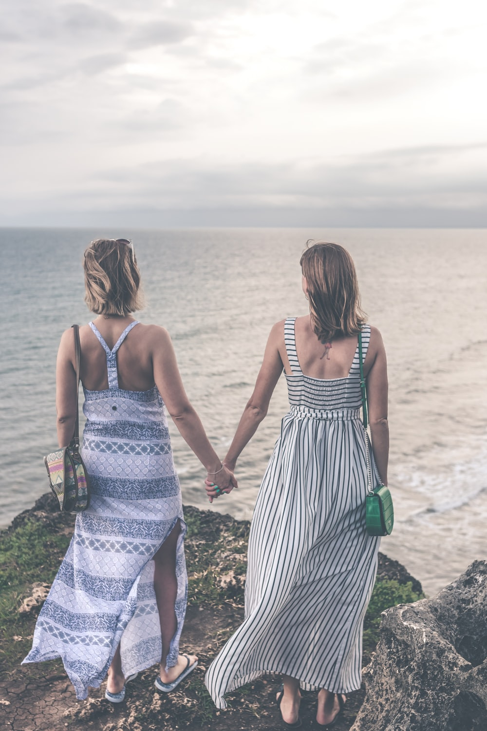 two woman in maxi dresses holding each other hand while standing on cliff