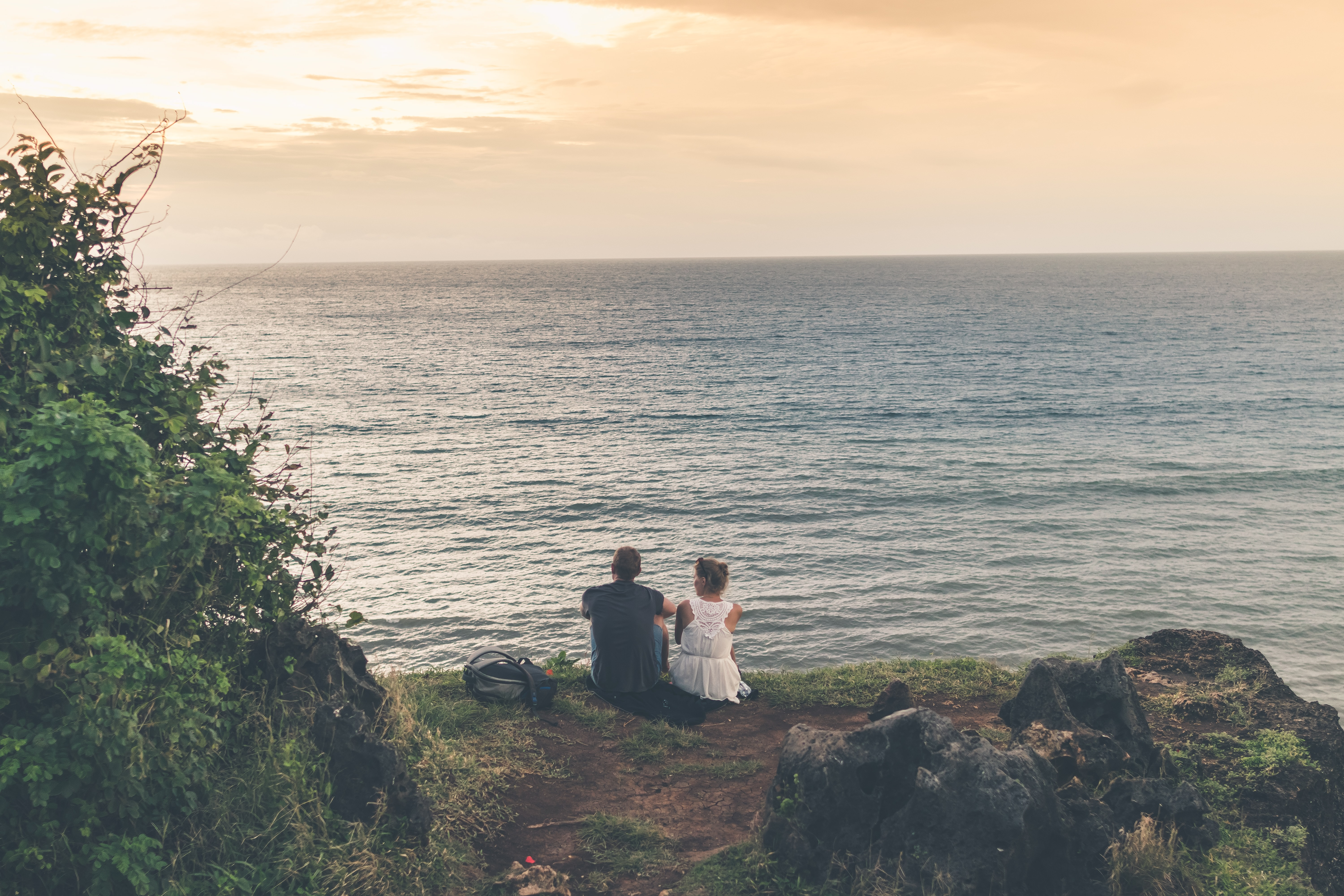 man sitting beside woman both facing in front of body of water