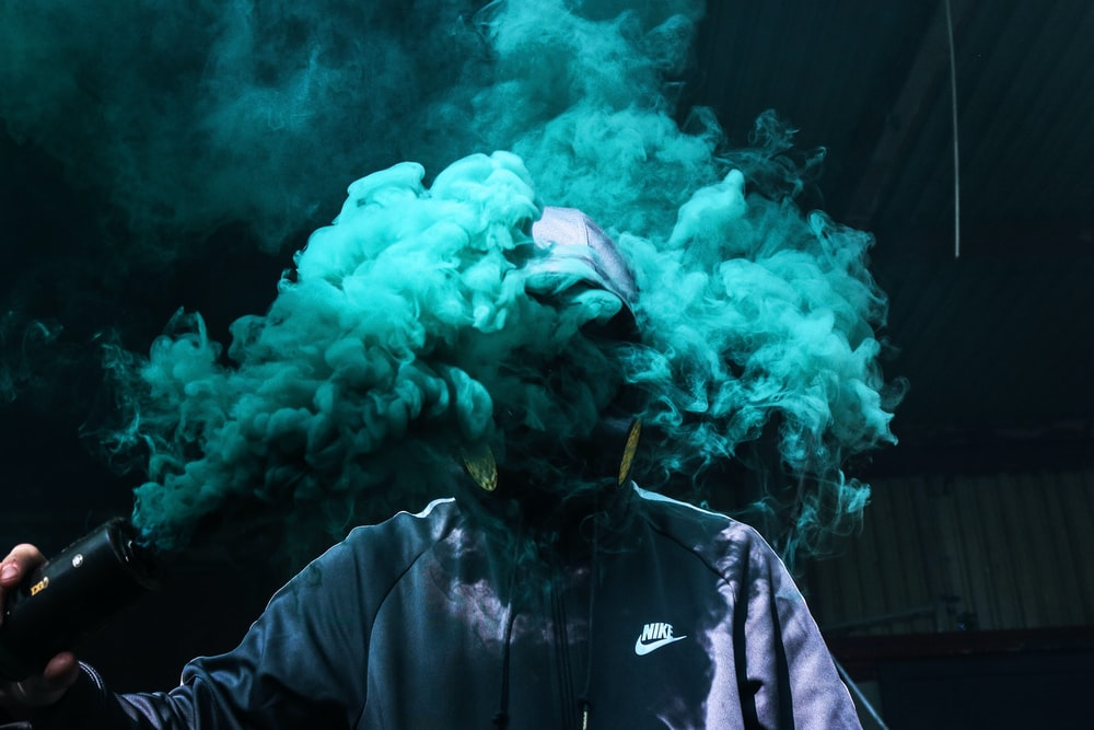 photo of person holding teal smoke grenade