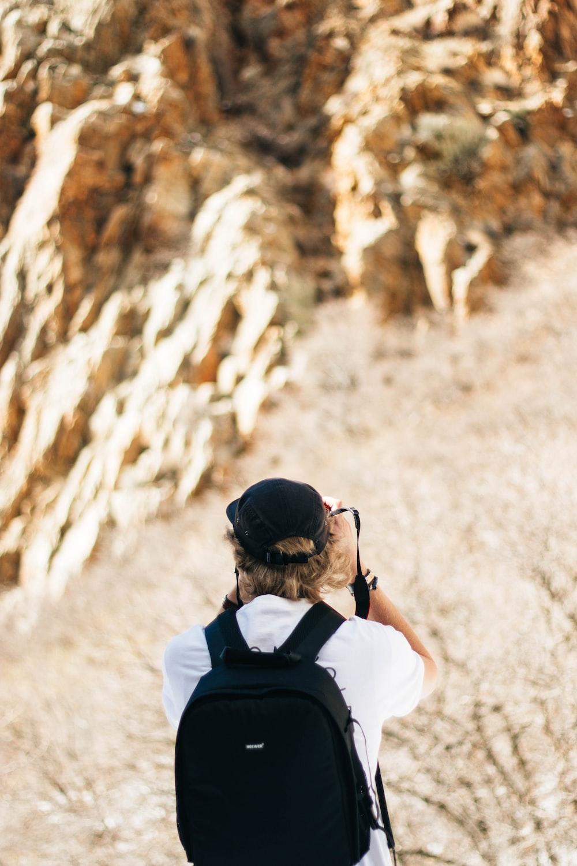 man taking photo of brown rocky mountains
