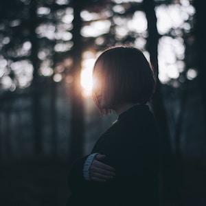 woman in black cardigan near trees
