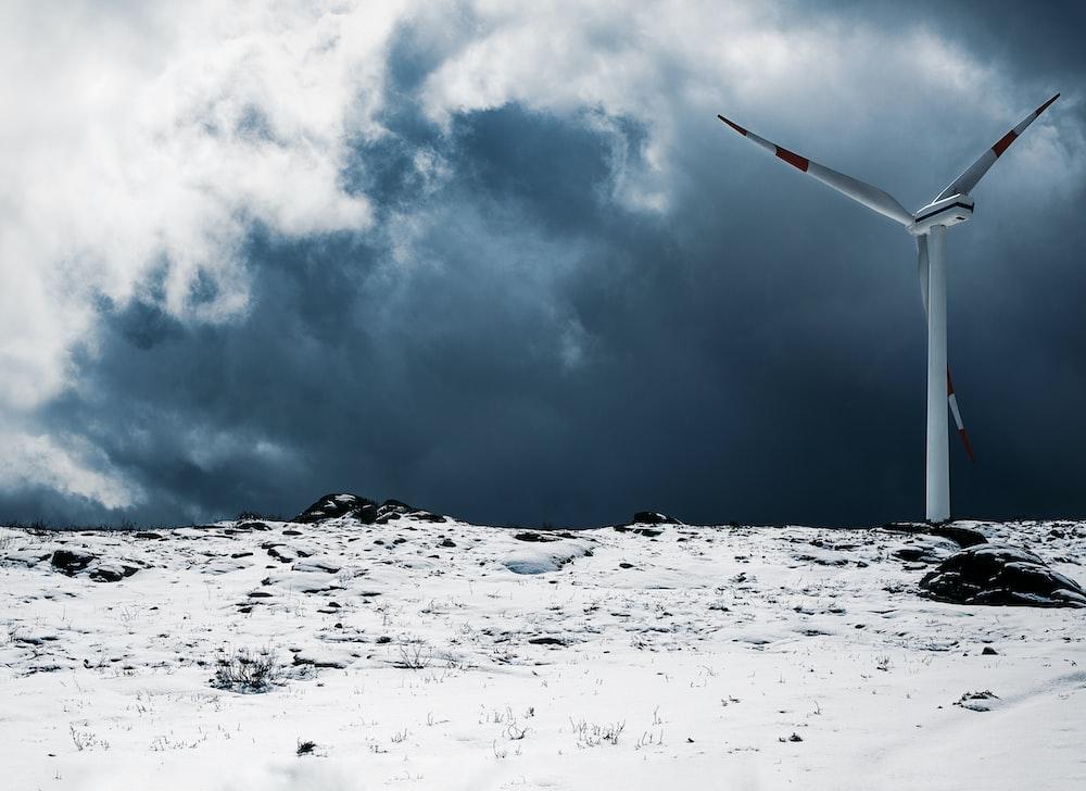 white wind turbine near snow field