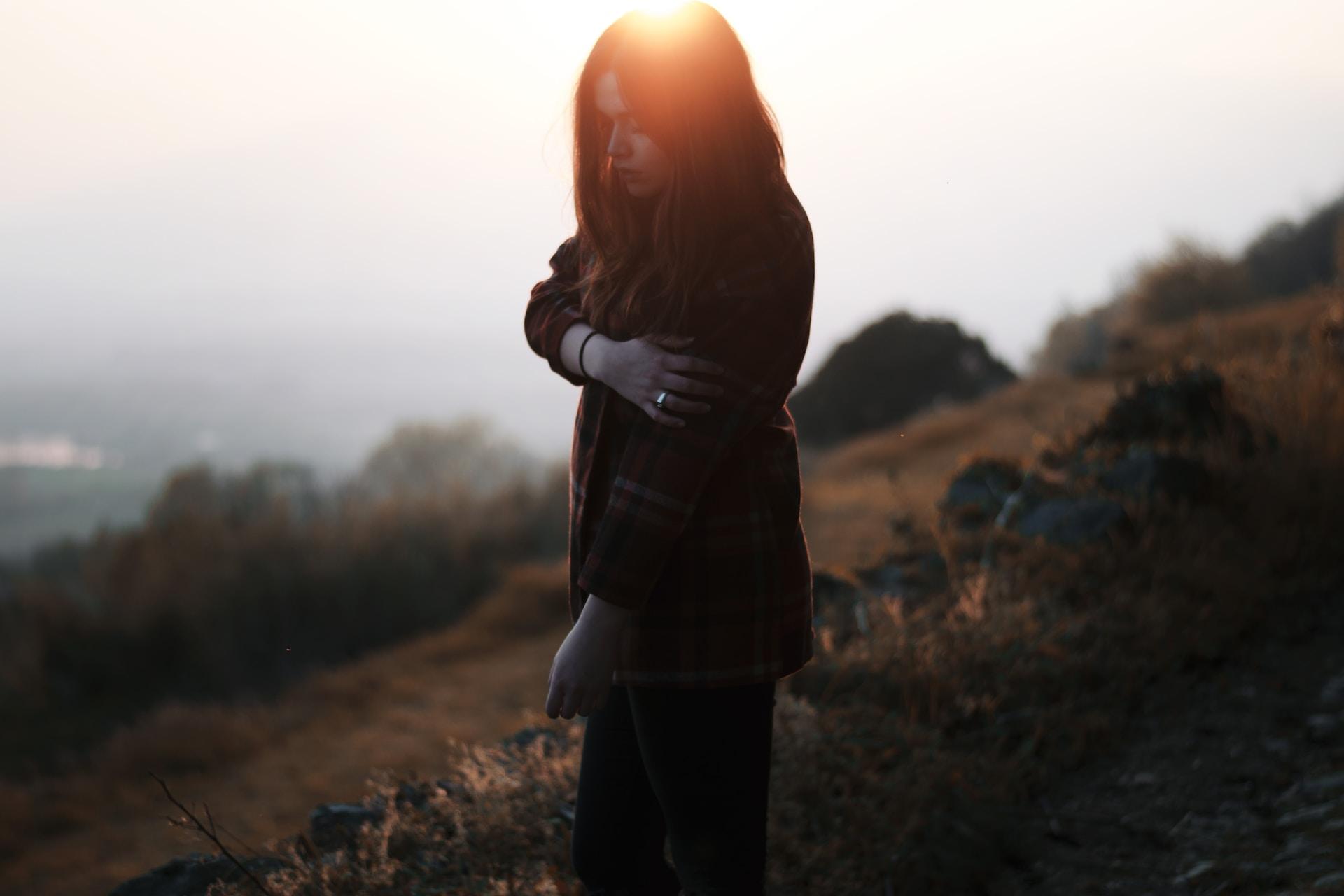 woman holding her shoulder