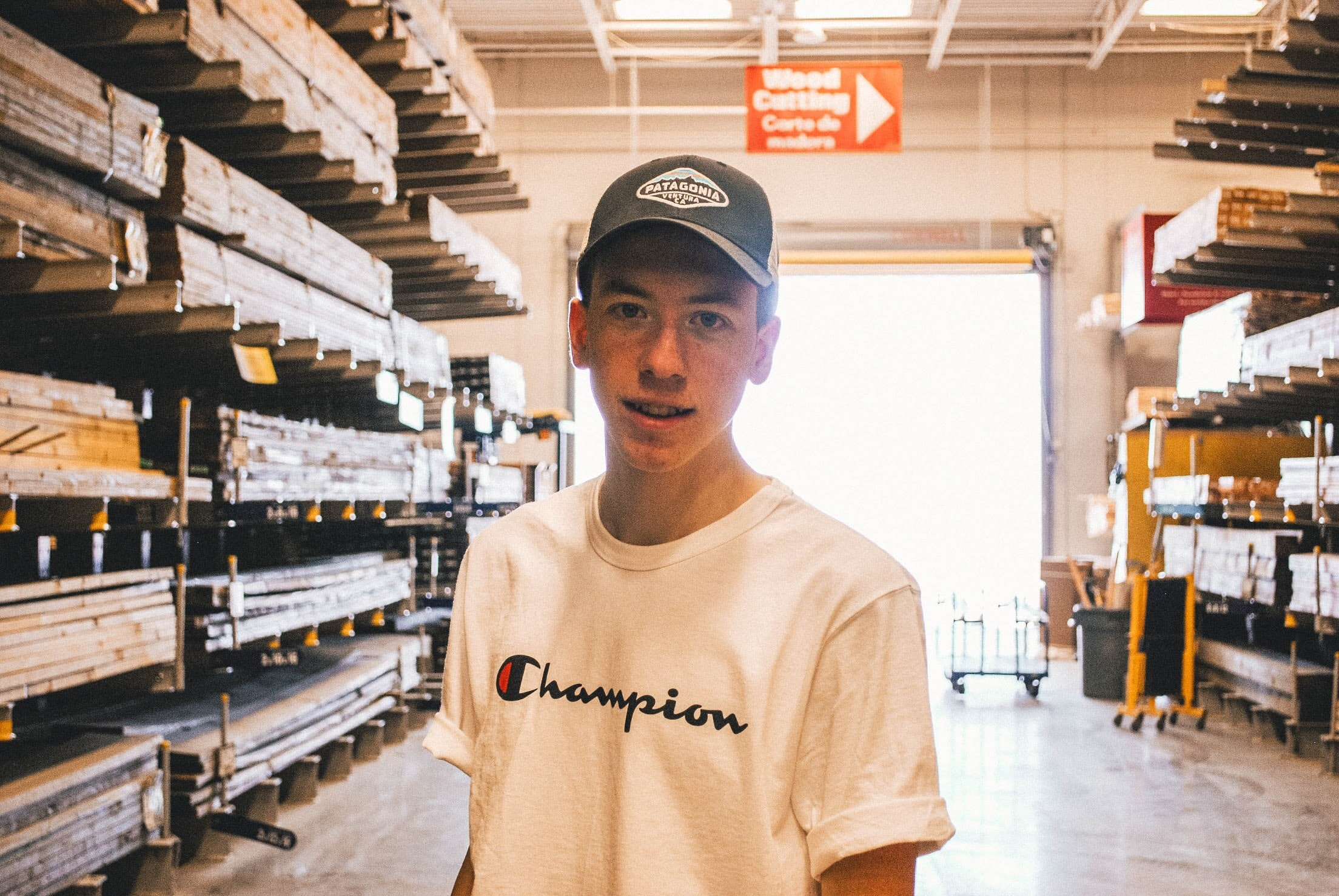 man wearing white Champion crew-neck tee shirt and gray fitted cap