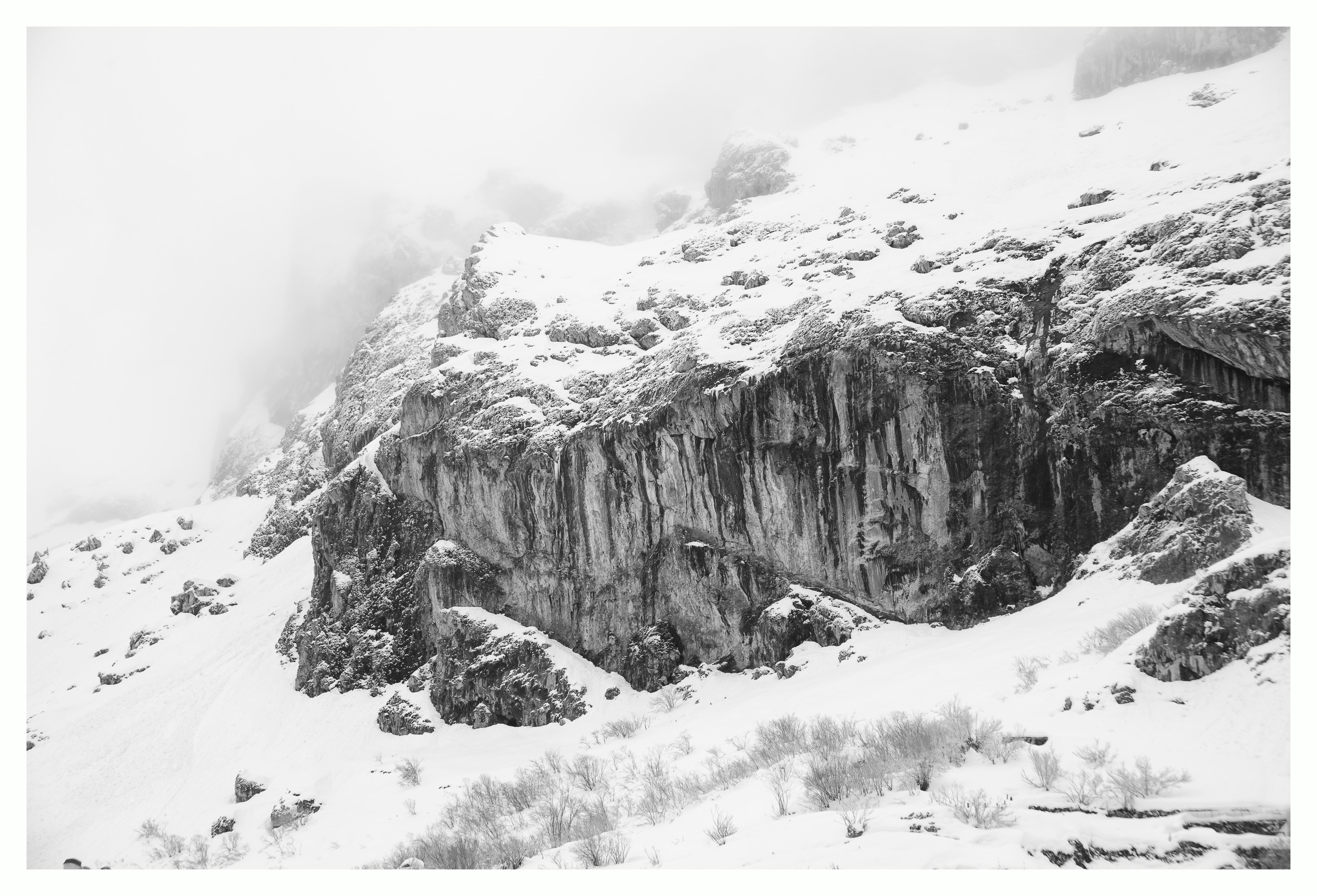 grayscale photography of snow covered cliff