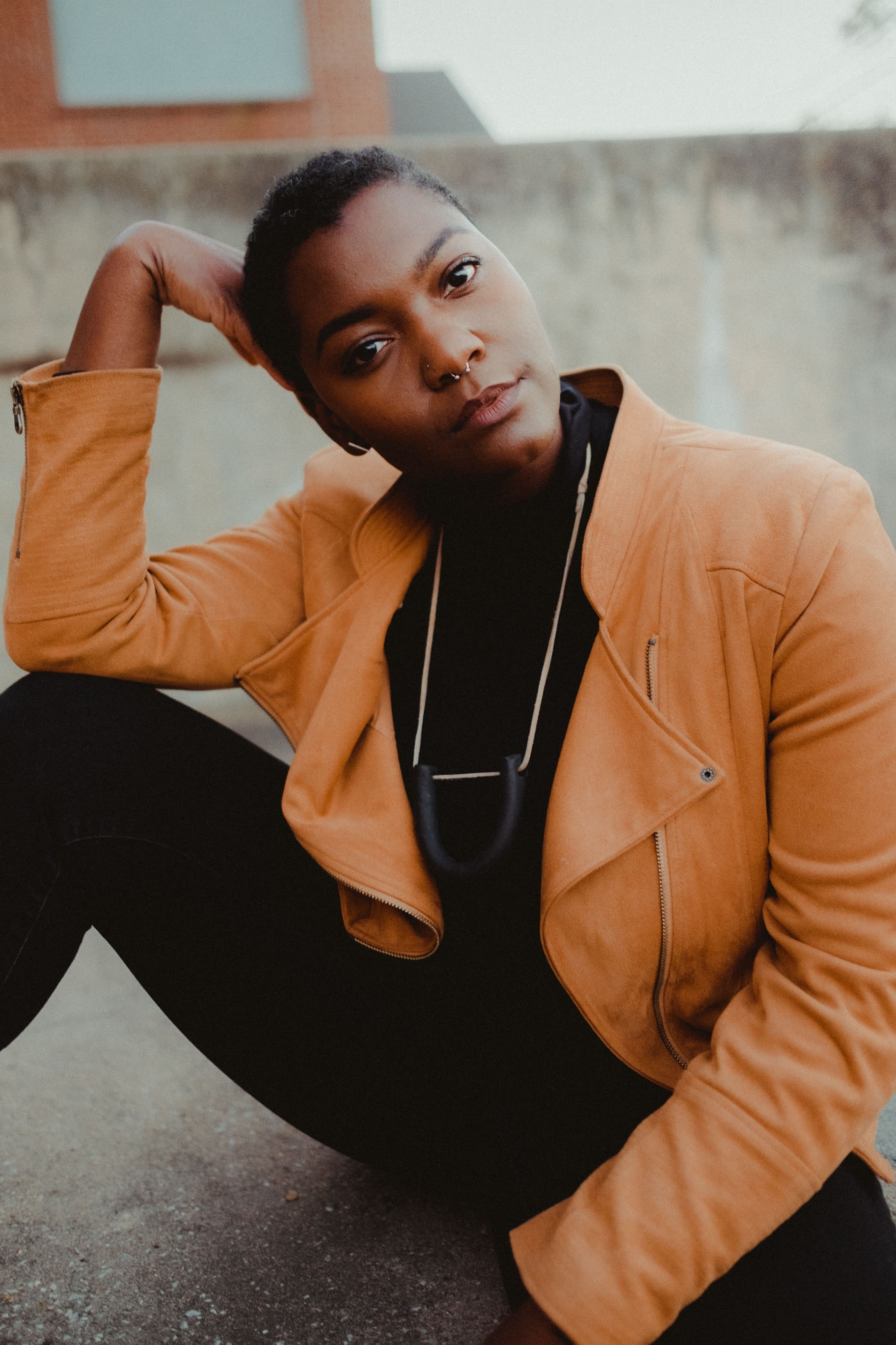 selective focus of woman in brown leather jacket sitting on gray pavement