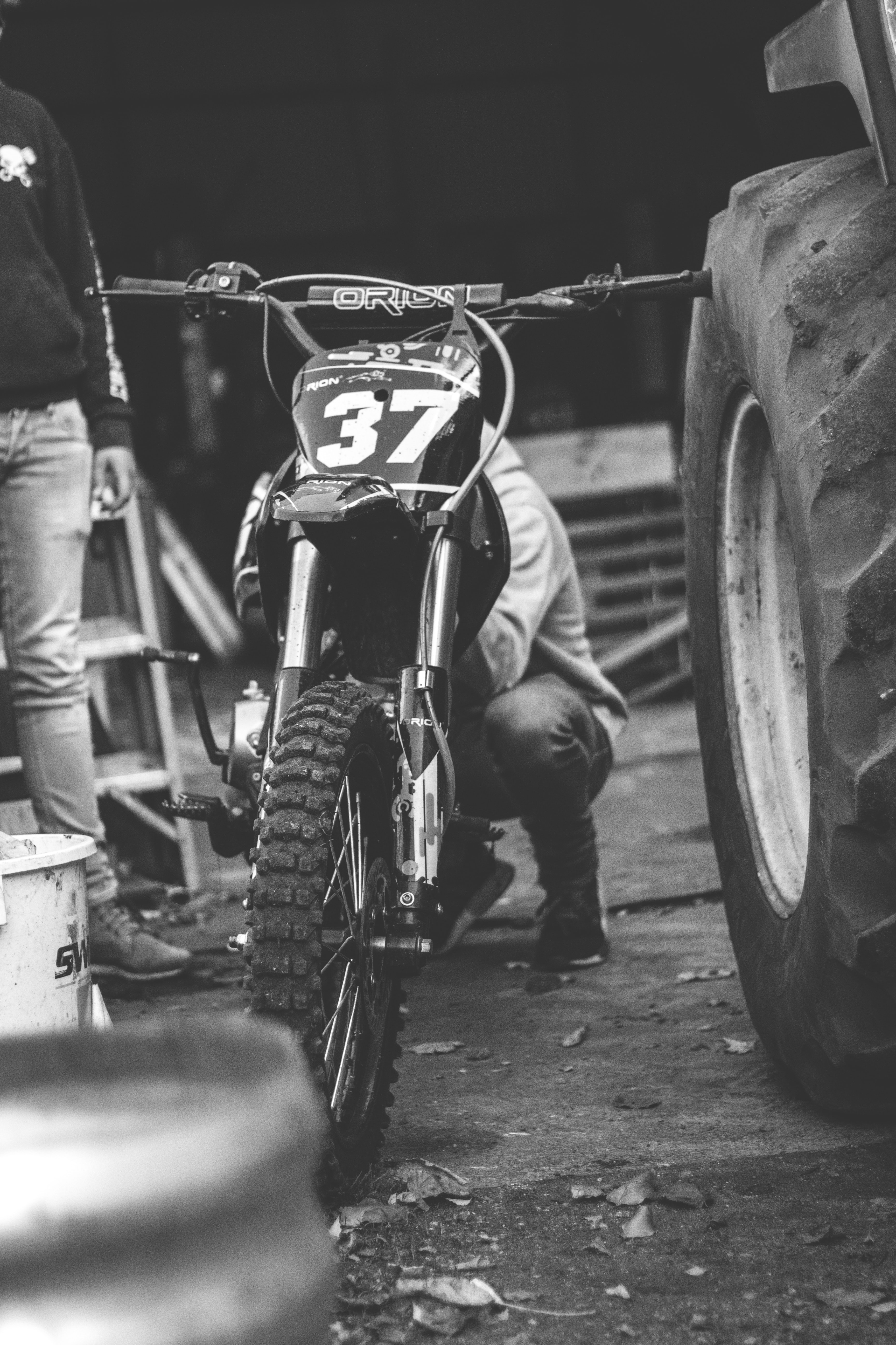 grayscale photo of person behind motocross dirt bike