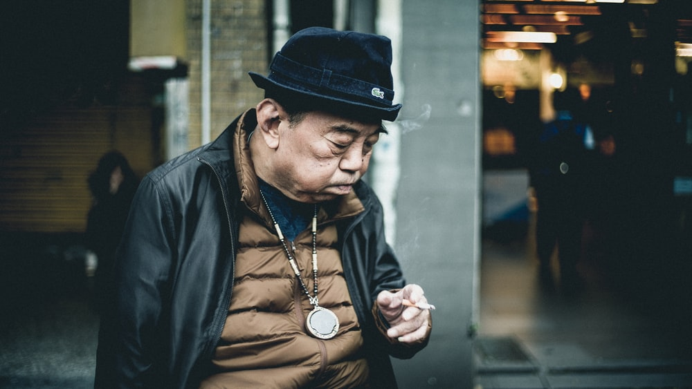 man in black leather jacket using cigarette