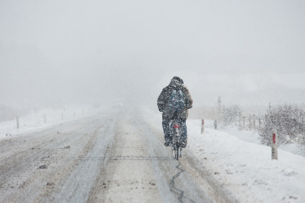 person riding motorcycle on snow coated road