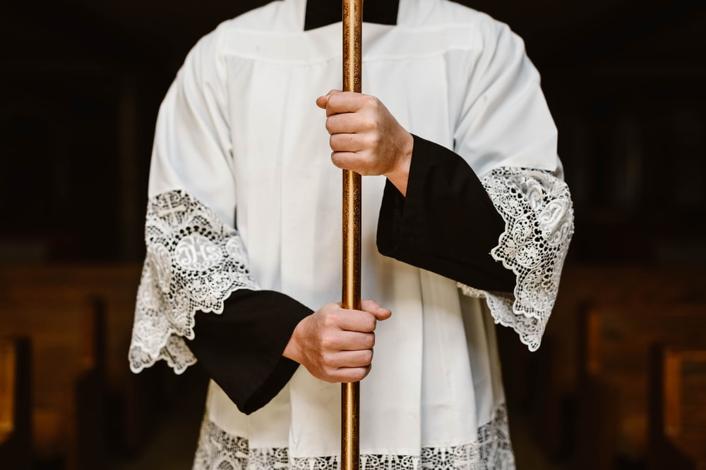 person wearing white surplice holding rod