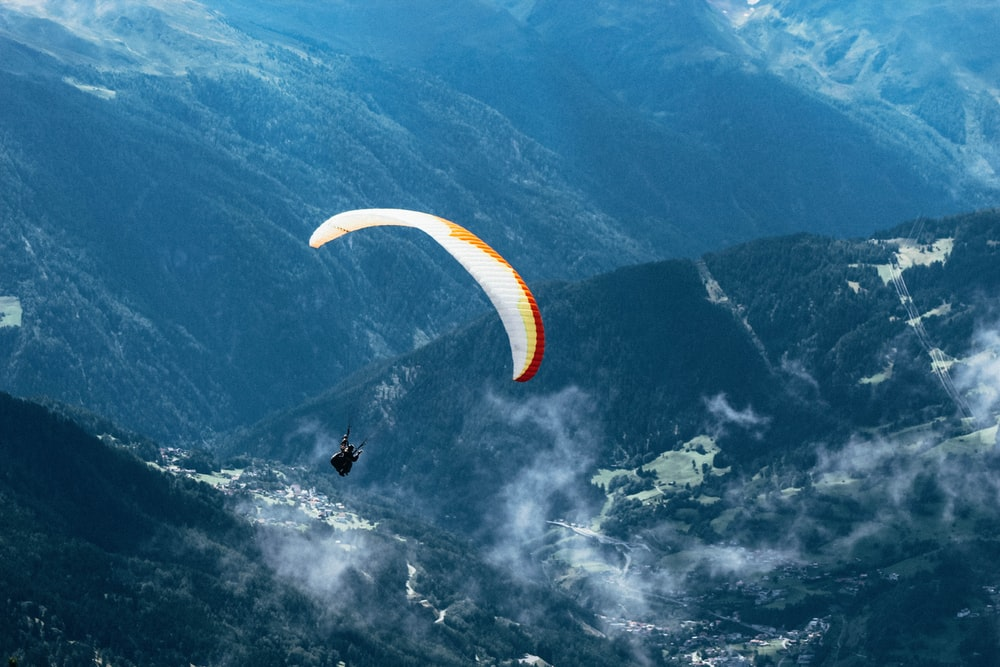 person paragliding over mountain ranges