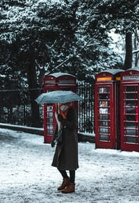 woman under umbrella near phone booth