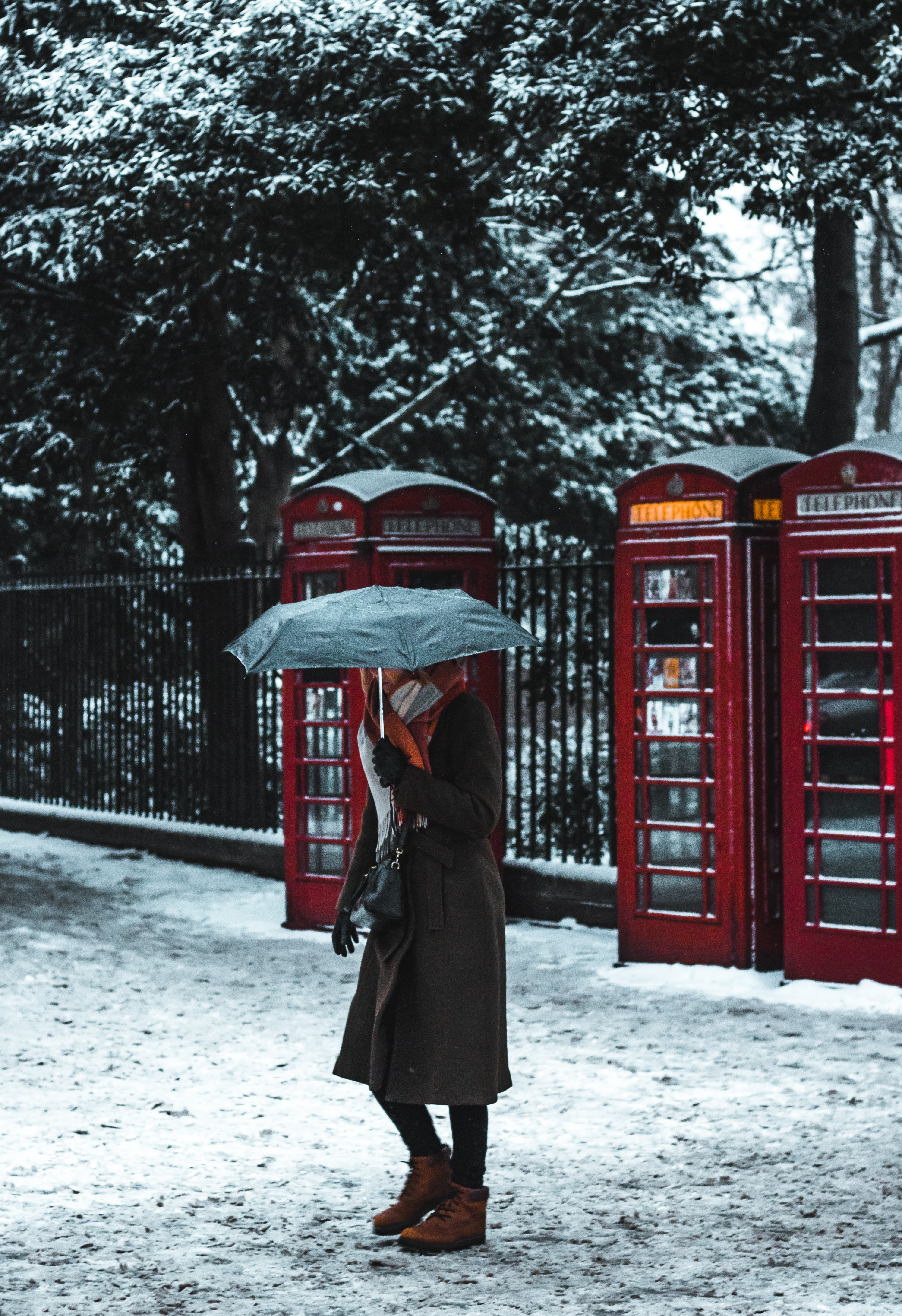 woman under umbrella near phone booth