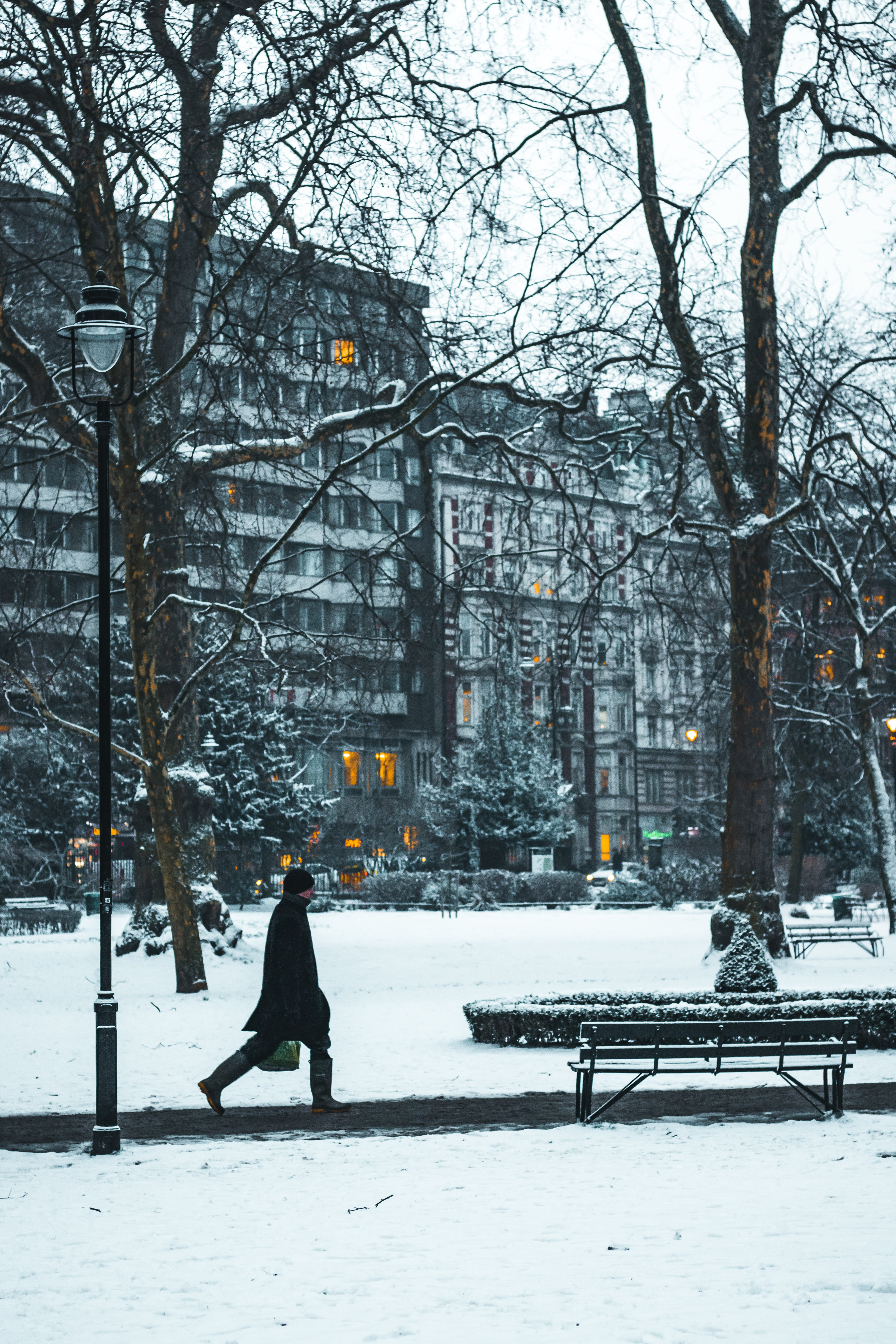 person walking near bench covered on snow