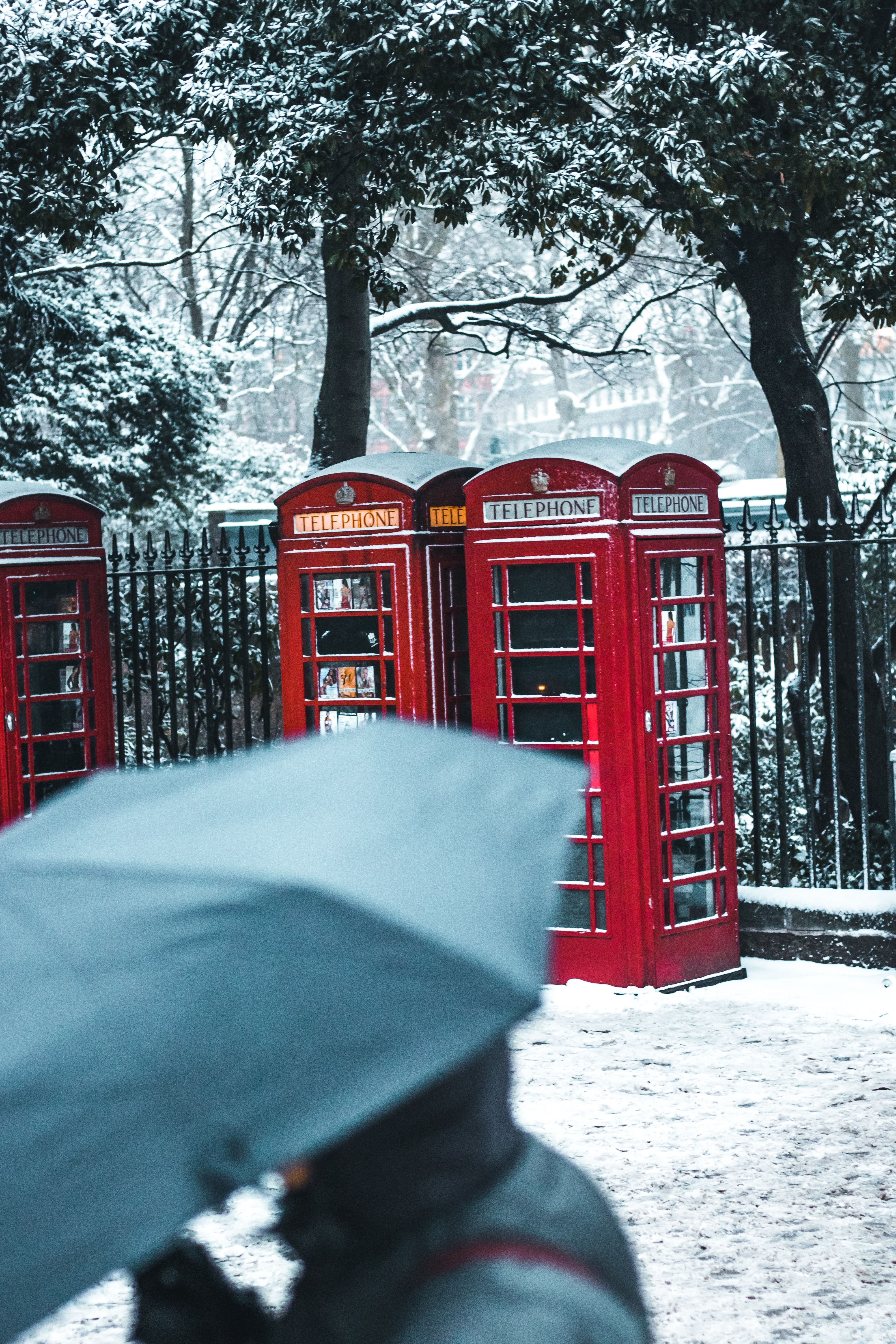 red telephone booths behind black steel fence during snow season