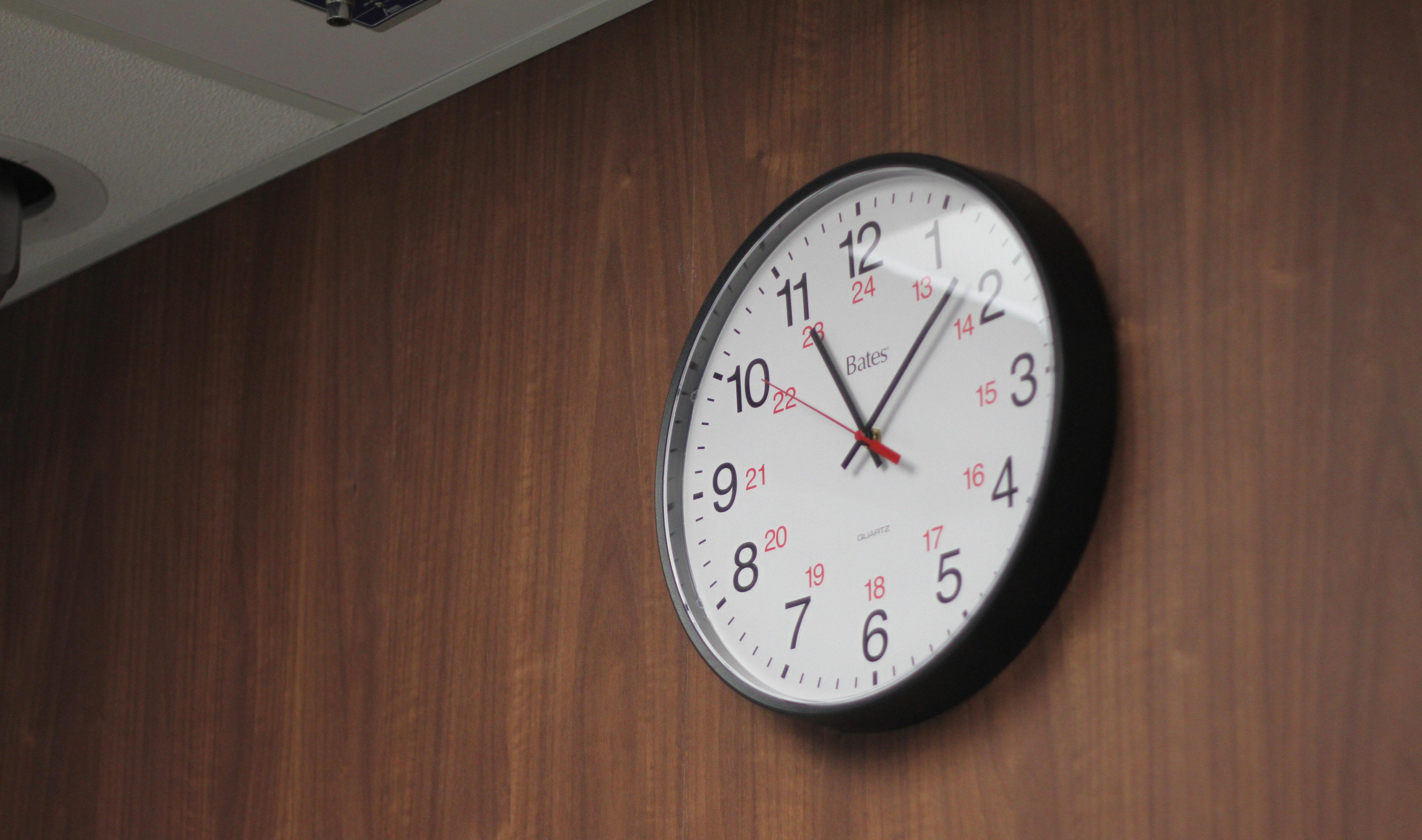 round black and white analog wall clock at 1:55