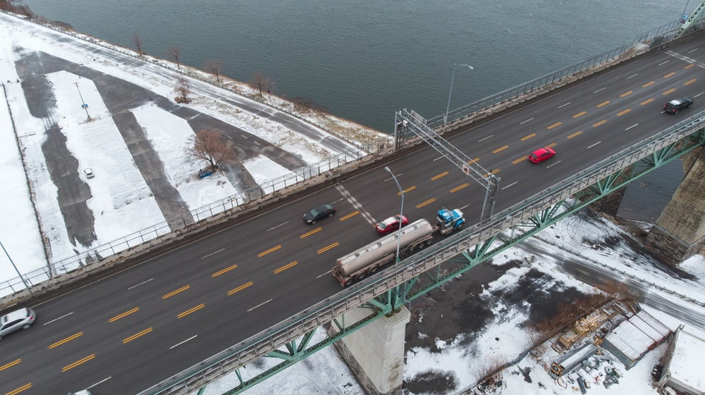 aerial photography of vehicles on steel bridge viewing blue body of water during daytime