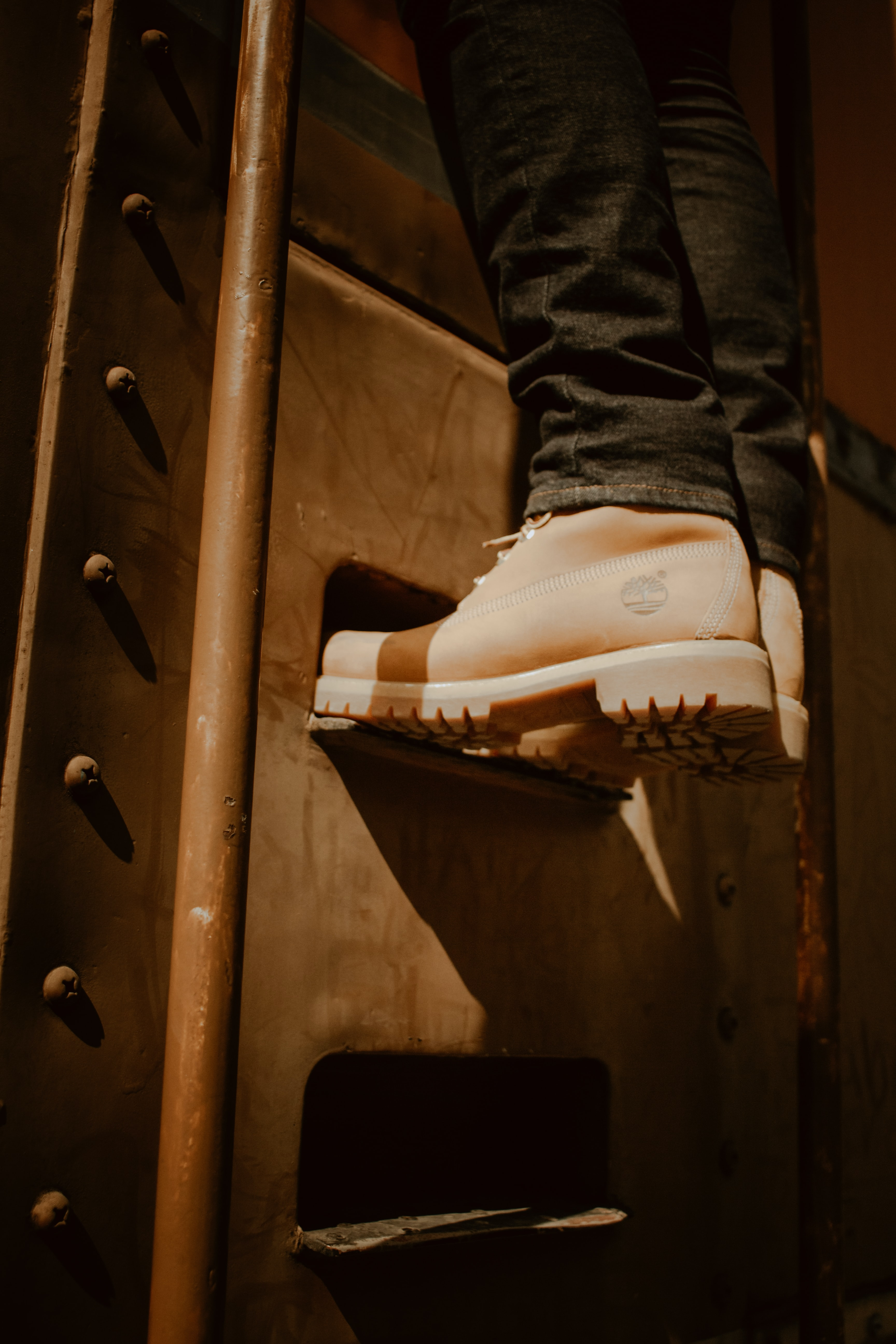 person wearing brown Timberland work boots climbing on stair