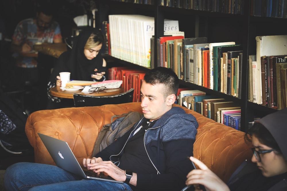 people sitting beside black wooden book case