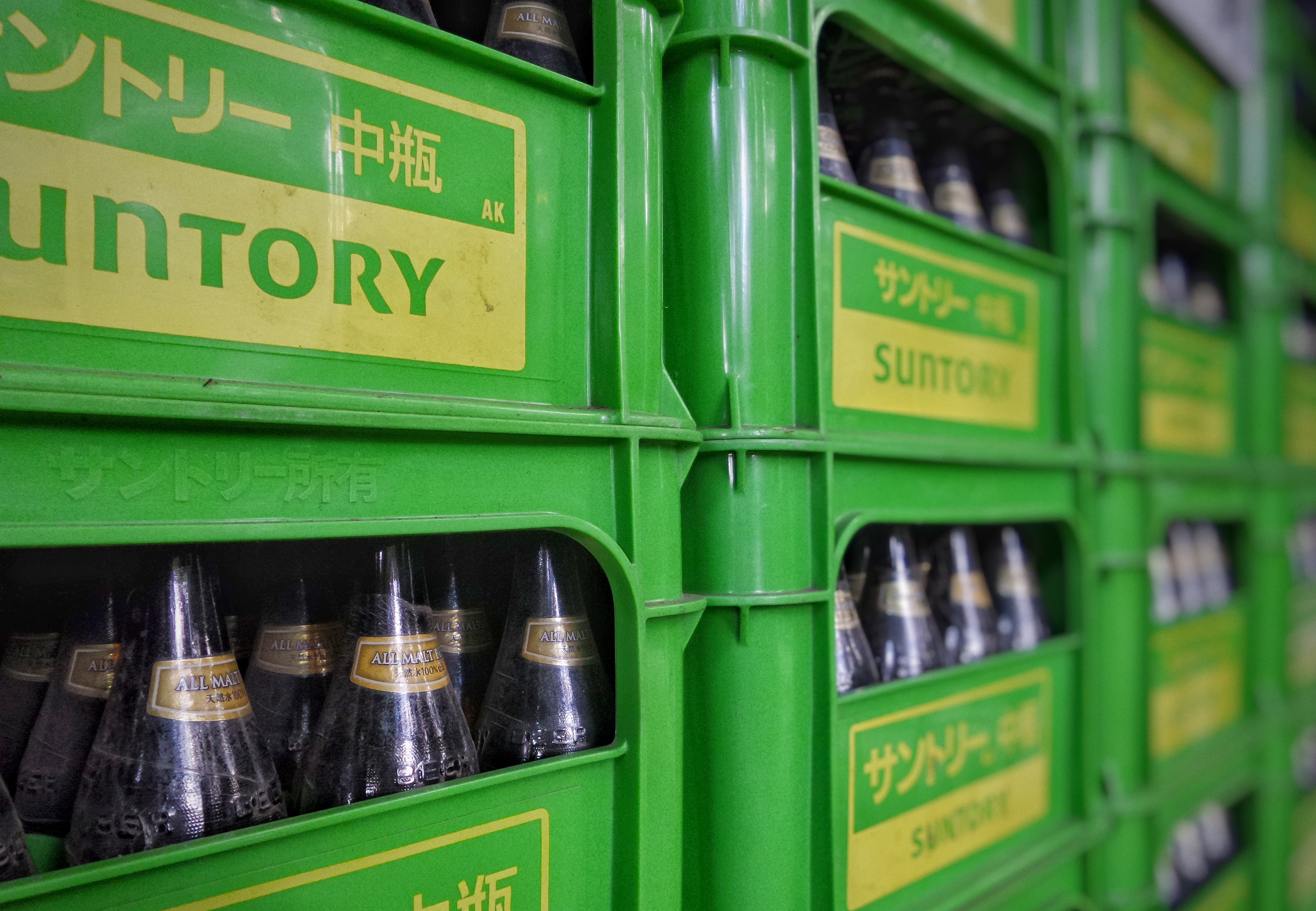 closeup photo of Suntory plastic bottle crates