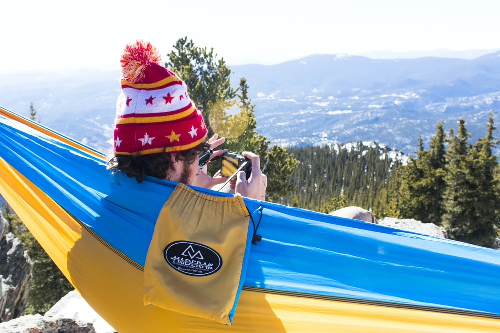 man in red and white bobble knit cap on blue and yellow hammock
