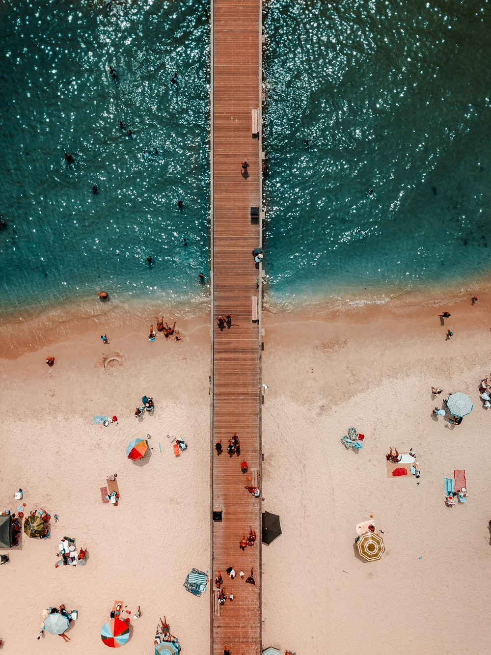 bird's-eye view photography of brown wooden dock on body of water