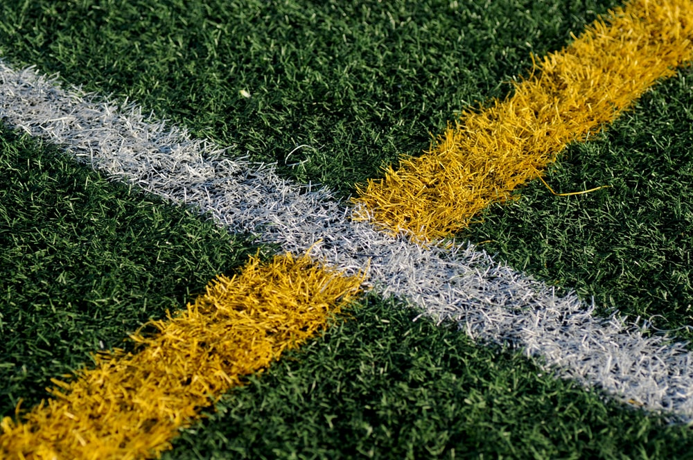 yellow and white line mark on green grasses