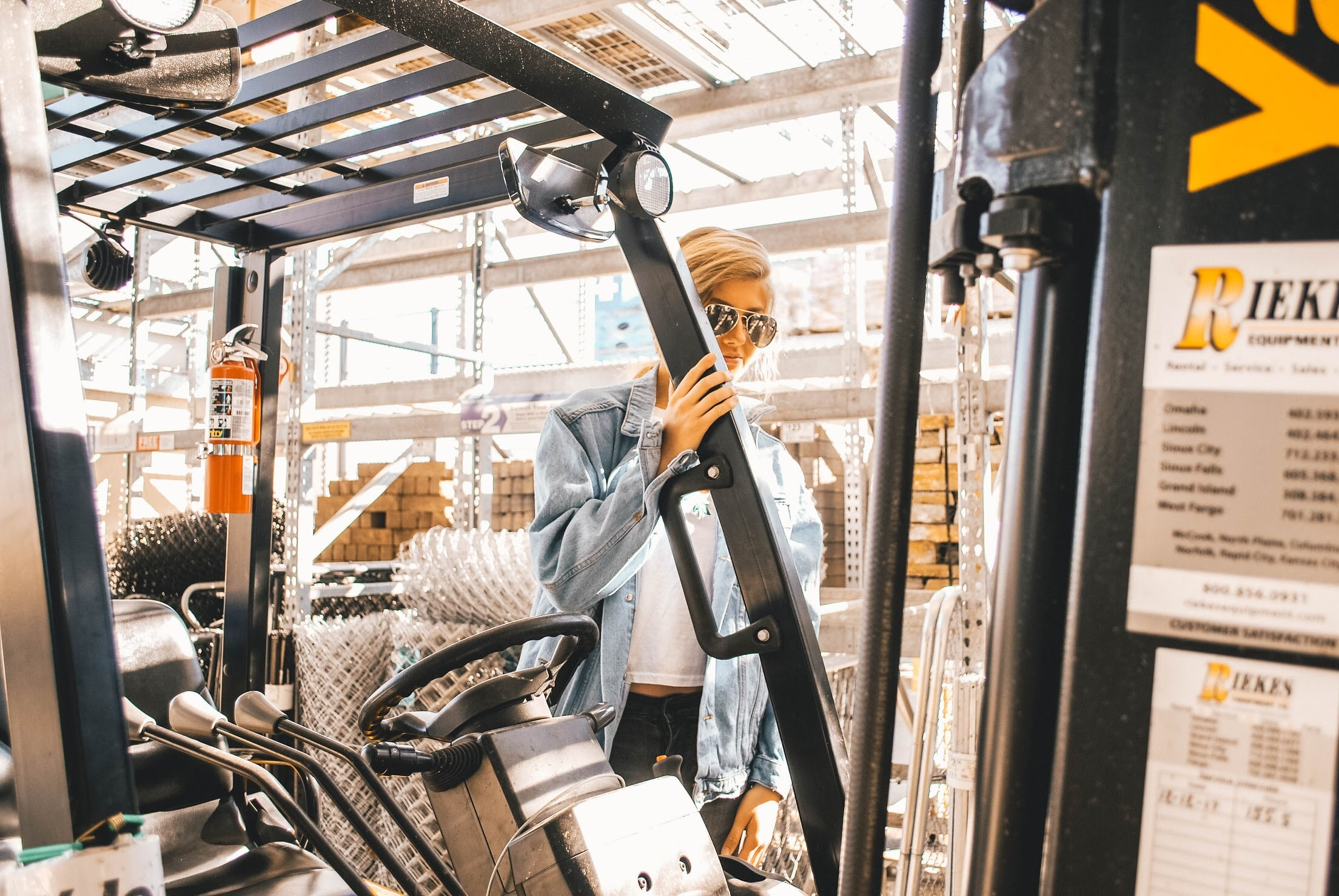 man in blue jacket holding forklift frame