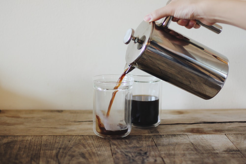person pouring coffee on glass cup