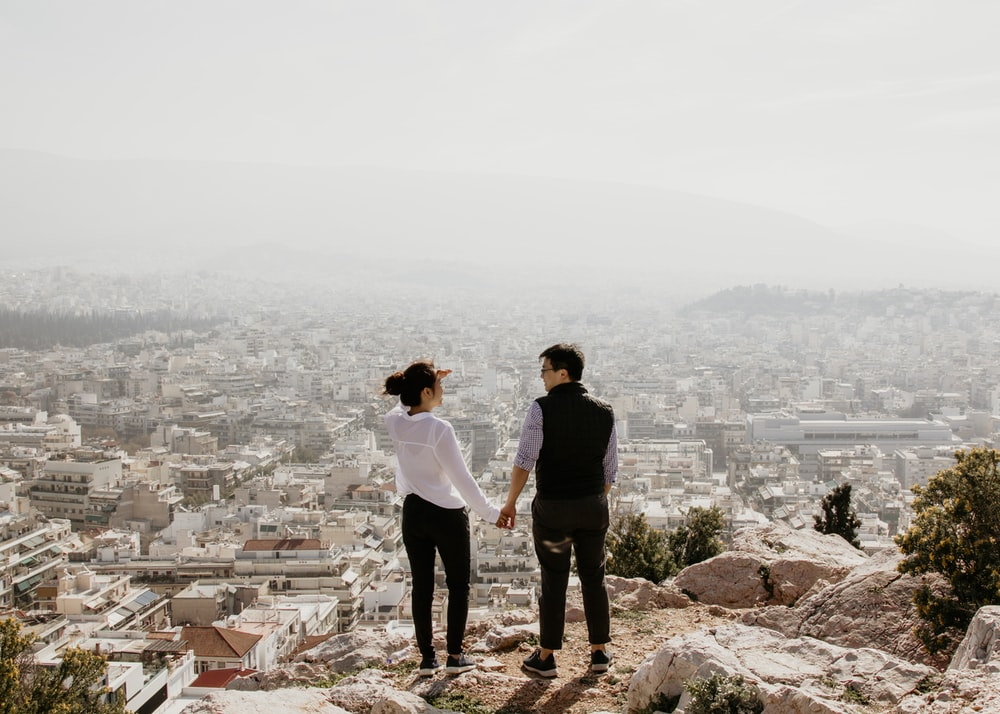 man and woman holding their hands together while standing on top of cliff