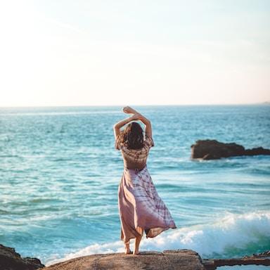 woman standing on cliff raiser her hands