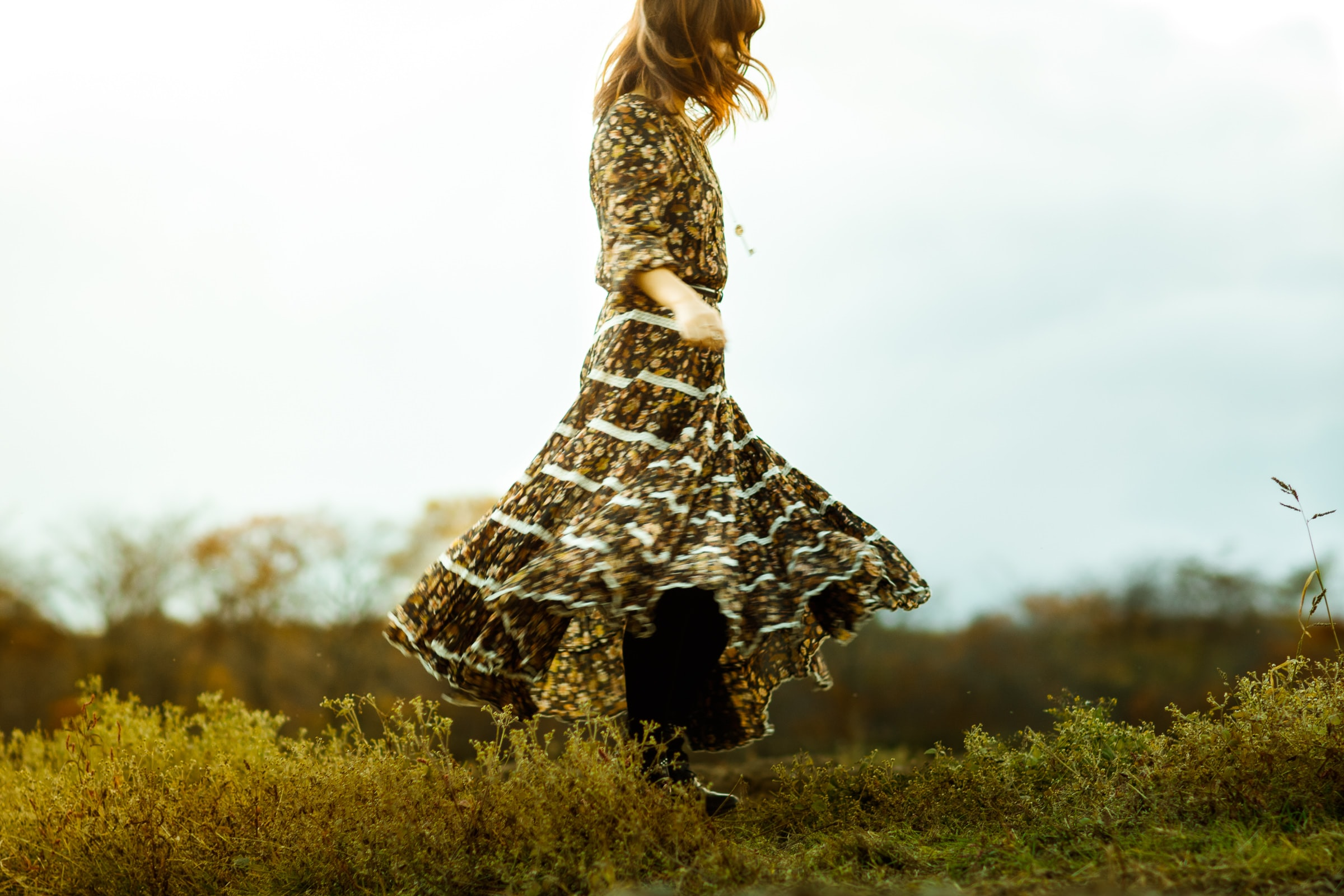 woman wearing brown and white long-sleeved long dress while standing on green grass