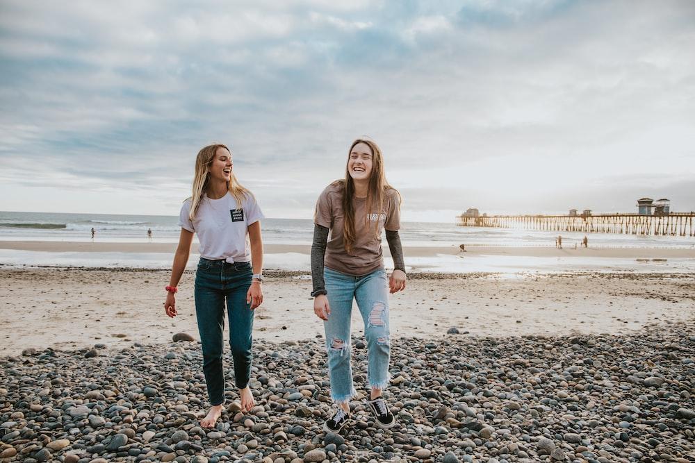 two women walking on pebbles