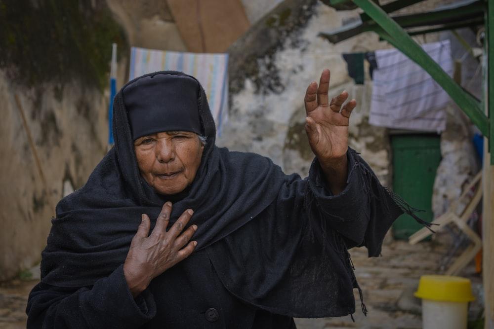 woman raising her left hand outside